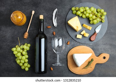 Yellow Maasdam cheese and white Camembert cheese with grapes, honey and bottle of wine on black background. Top view. Concept serving of cheese.
