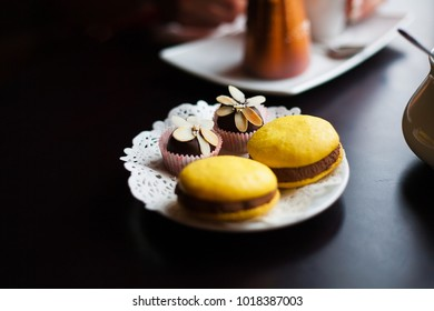 yellow macaroons and chocolate sweets lie on a white plate.