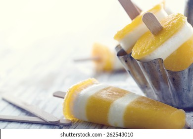 Yellow mango homemade popsicles on white wooden background with hazy vintage editing