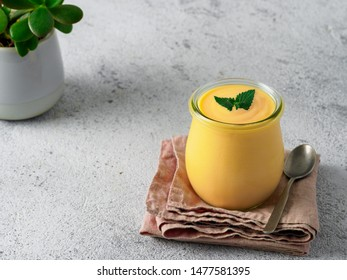 Yellow mango lassi on gray background. Indian mango yogurt drink with copy space left.
