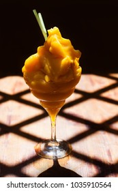 Yellow mango margarita cocktail. Frozen mango margarita daiquiri with green straw. Brown wooden background. sunny day shadows pattern.