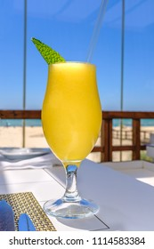yellow mango smoothie fruit drink in a glass with a mint leaf and a straw on a table near a beach