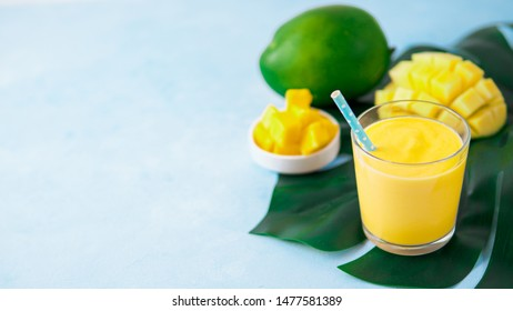 Yellow mango yogurt or smoothie on blue background with copy space left. Turmeric Lassie or lassi in glass. Banner