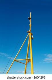 The yellow mast of a small ship on a blue sky background