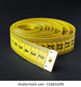 Yellow measure tape om black background