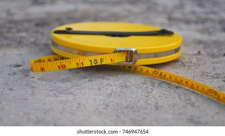 Yellow Measure tape placed on the floor.