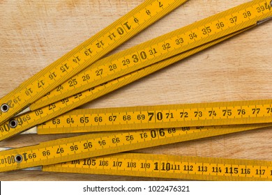 Yellow measuring stick on an old wooden table