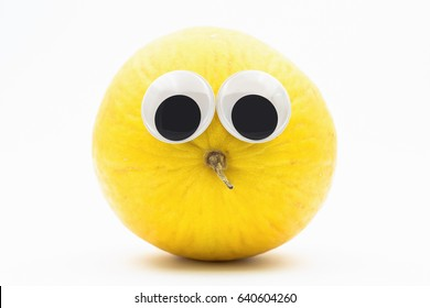 yellow melon with googly eyes on white background