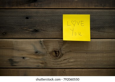 """Yellow memo stick """" LOVE YOU """" isolated on wood wall background with soft shadow"""