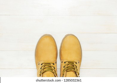 Yellow men's work boots from natural nubuck leather on wooden white background top view flat lay with copy space. Trendy casual shoes, youth style. Concept of advertising autumn winter shoes sale shop