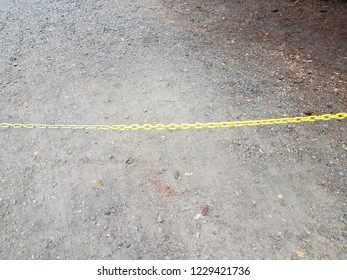 yellow metal chain with dirt and rocks and stones