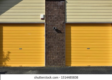 Yellow metal garage gates with brick wall between them and weatherboard cladding above.