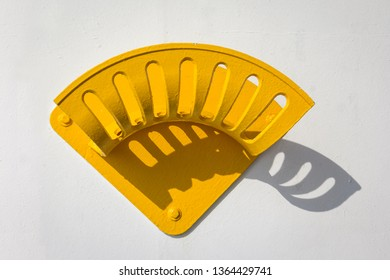 A yellow metal suspension on a wall on a ship. The colour contrast of white and yellow and the shadows are beautiful.