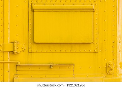 yellow metal wall with closed hatch and rivets. abstract industrial background