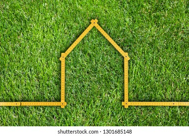 Yellow meter ruler folded as house on green grass