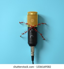 Yellow microphone with red barbed wire. Idea and concept for the topic of censorship or freedom of the press.