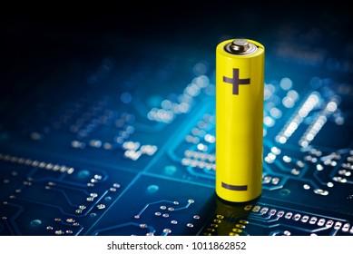 Yellow mignon AA battery on the blue printed circuit board. Macro shot