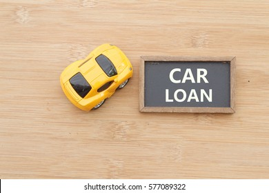 Yellow mini toy car with mini chalkboard on wooden background. CAR LOAN written on the chalkboard. Conceptual.
