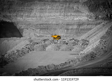 Yellow mining truck transports coal form large open cut mine, Fossil fuel industry, Environmental challenge.
