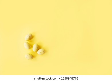 Yellow miniture speckled chocolate easter eggs coated in hard shell on yellow background, with copy space