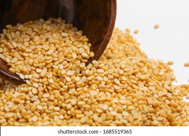 yellow moong mung dal lentil pulse bean in wooden bowl on white background