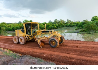 Yellow motor grader Road working on road construction site of new road.
