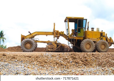 Yellow Motor grader (Road grader) working at road construction site.