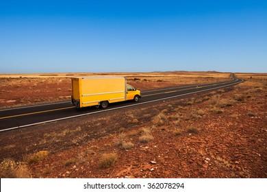 Yellow moving truck on desert highway, Arizona
