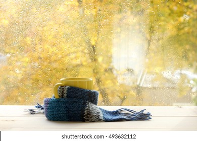 yellow mug in a warming scarf in front of a window with drops after rain in autumn / warming tea with mood