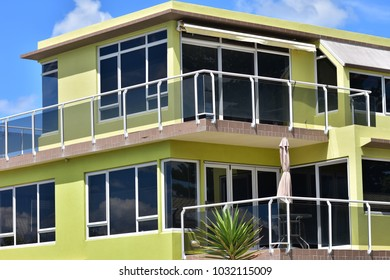 Yellow multi-story holiday house with verandas protected by glass railing and tinted glass windows.