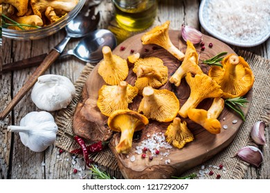 Yellow mushrooms chanterelle in vintage plate with forest plants on dark kitchen table