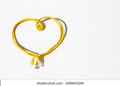 Yellow network cable folded in the shape of a heart isolated on white. Safer Internet Day. World Telecommunication and Information Society Day.
