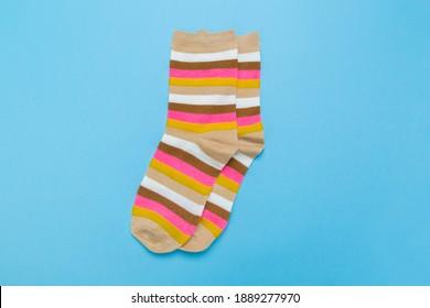 yellow new socks stacked on a blue background. top view.