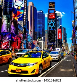 Yellow New York City Taxi cab driving through Times Square on a beautiful summer day. Manhattan, New York. USA - June 2, 2019