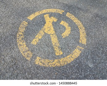 yellow no parking sign or symbol on asphalt