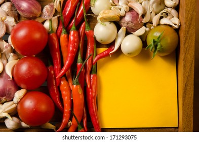 Yellow note with chilli,tomato,shallot and garlic on wood background