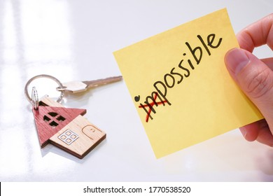 Yellow note with wording Impossible which crossed out the first two alphabet holded by a hand and house key chain on white background ,selective focus , home buyer and home loan concept