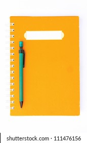 Yellow notebook with green pencil on white background