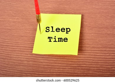 "Yellow Notepad with arrow Dart and text ""Sleep Time"". Wooden background"