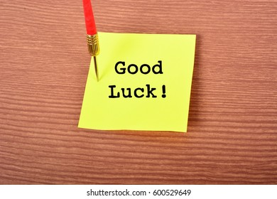 "Yellow Notepad with arrow Dart and text ""Good Luck!"". Wooden background"