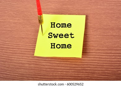 """Yellow Notepad with arrow Dart and text """"Home Sweet Home"""". Wooden background"""