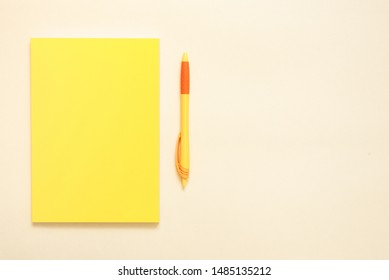 Yellow notepad and pen on orange background.