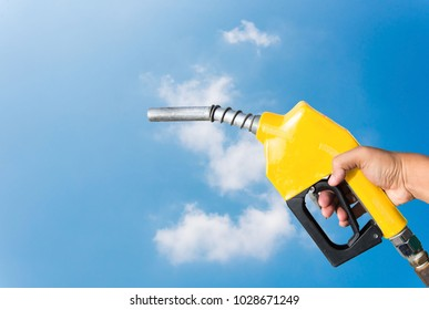 Yellow nozzle handle holding a separate from on a sky background.
