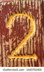 yellow number 2 carved into rustic wood painted red