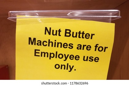 yellow nut butter machines are for employee use only sign on plastic container