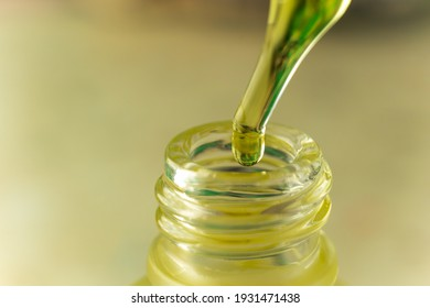Yellow oil drips into a glass bottle from a pipette. Cosmetic oil. A drop of hemp oil. Dropper with oil close-up.