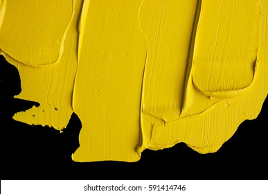 Yellow oil paint isolated on a black background