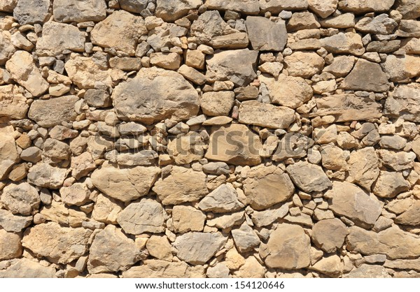 yellow old wall made of big and little rough stones without cement