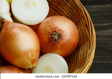 Yellow onions  in basket on wooden background.