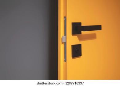 Yellow open door with black handle, grey wall